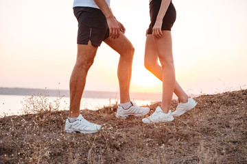 Young fitness couple standing during sunset on hill
