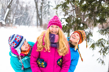 Happy friends having fun in winter cild snowing weather at park