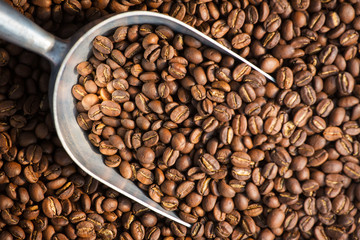 Fresh roasted coffee beans background with the metal scoop