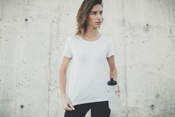 Young fitness girl wearing blank white t-shirt with empty area for design or content, mockup of template white t-shirt, female jogger resting after active workout outside, concrete wall in background