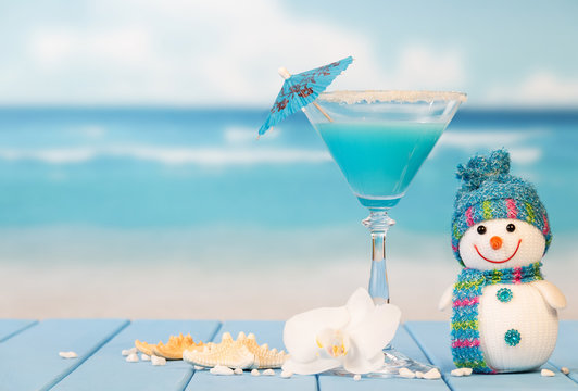 Cocktail, snowman, starfish and orchid flower on background of sea.