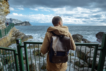 Traveller man with backpack enjoying view of sea