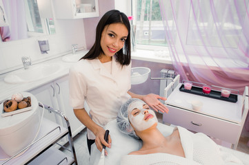 Spa concept. Young woman with nutrient facial mask in beauty salon