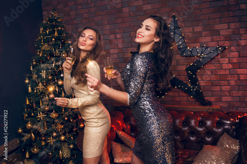 a6df3747ea50 Two smiling girl in dress waiting for Christmas and drinking champagne with  sparklers in their hands. Wishing you a prosperous New Year! Christmas time!