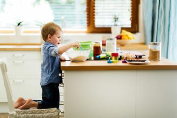 Toddler preparing food in kitchen