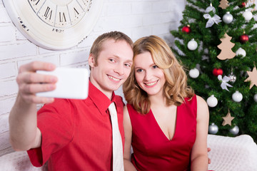 young couple taking selfie photo in front of Christmas tree