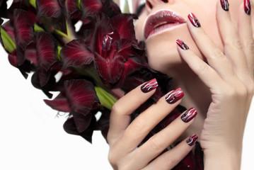 Маникюр с белыми волнистыми линиями,чёрными стразами и плавным переходом от тёмного бордового до светлого цвета лака на ногтях квадратной формы и гладиолусом в женской руке.