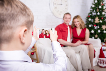 little boy taking photo of his parents in front of Christmas tre