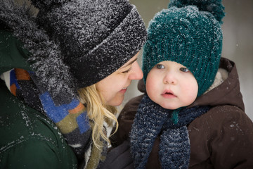 Portrait of young mother and little toddler boy in the winter forest. Family enjoying winter. Child and woman watching falling snow outdoors. Winter, Christmas and lifestyle concept.