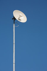 Wireless antenna dish and blue sky.