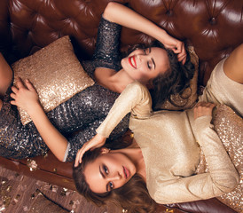 Two  girls lie on the bed and smiling. Christmas feeling. After Christmas party.