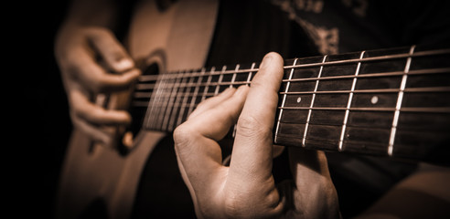 Close up hands on the strings of a guitar