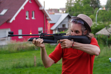 Young man shoot with air rifle outside