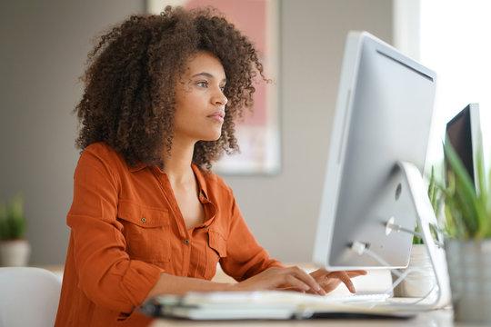 Cheerful businesswoman working on desktop computer