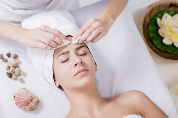 Young woman enjoying facial massage at spa salon