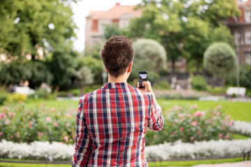 Man taking a photo with smart phone. Picture of beautiful building with blooming garden, tourist.