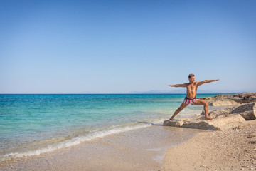 Adult man practicing yoga on the beach in Greece, in position wa