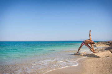 Adult man on the beach in Greece, morning yoga practice