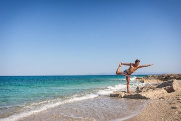 Adult man in yoga position on the waterfront in Greece
