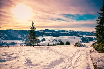Winter sunset mountain landscape. Mountain trail and hills covered with snow.