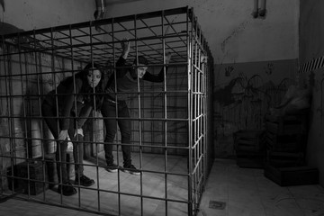Black and white picture of victims imprisoned in a metal cage tr