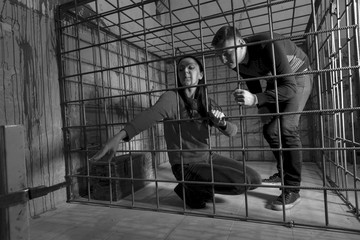 Black and white picture of victims imprisoned in a metal cage, g