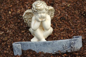 little angel sculpture decorate in small garden with a sign in front it