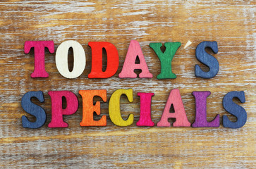 Today's specials written with colorful letters on rustic wooden surface