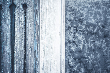 Winter background with frost pattern on rustic window with copy space
