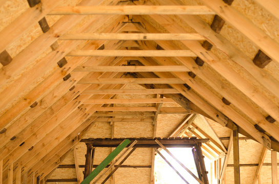 Raising roof truss to second story of new residential construction. Interior view of a wooden roof structure. roof preparation of OSB.