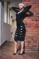 Woman standing near brick wall in dress
