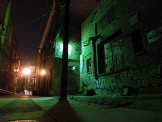 Creepy urban alley illuminated at night with graffiti