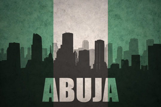 abstract silhouette of the city with text Abuja at the vintage nigerian flag