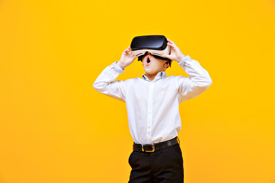 Kid in formal outfit wearing VR glasses putting hands out in excitement isolated on orange background.