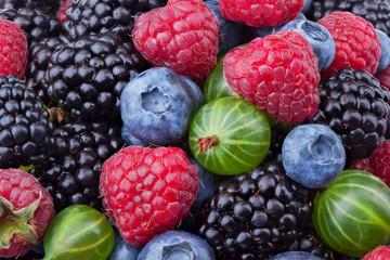 Blueberries, raspberries, blackberries and gooseberries background shot top down. Top view.