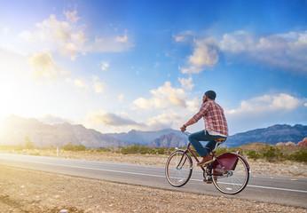 man riding bike into nevada sunset on empty highway