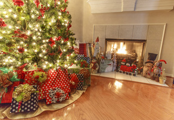 Christmas interior design. Living room with Christmas tree, wrapped gifts and glowing fireplace. Horizontal panorama.