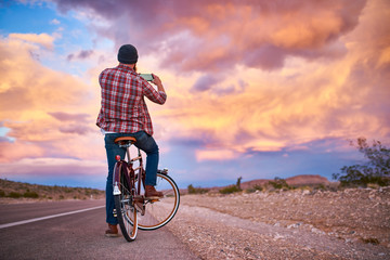 man on bike stopping to take photo of awesome sunset with smartphone
