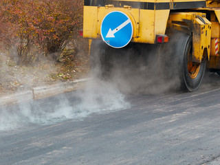 Road construction works with tyred road roller finishes asphalt