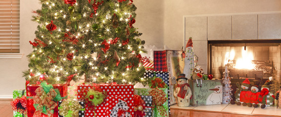 Christmas tree with wrapped gifts next to a fire place