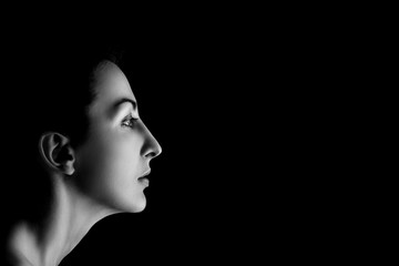 serious female profile on black background with copyspace