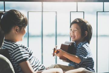 Asian girl playing ukulele near the window