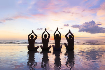 Group of people practicing meditation and yoga, beach, sunset, harmony