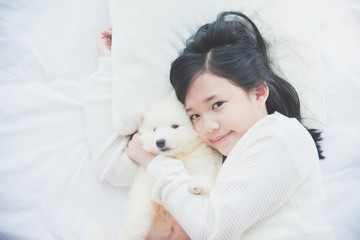 asian girl lying with siberian husky puppy on bed..