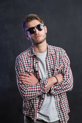 Portrait of a relaxed young man with checkered shirt and sunglas