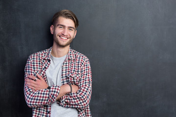 Happy young man standing with arms crossed over blackboard backg