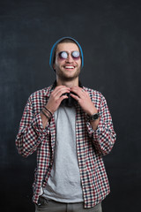 Carefree music lover. Joyful young man in headphones smiling aga