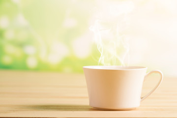 Coffee cup and smoke background green nature bokeh.