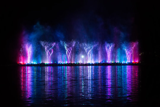 Beautiful fountain dancing show with reflection on water at night.