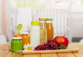 Bottles with milk, juice and puree, apple, grapes on kitchen.
